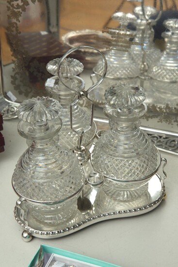 A SILVER PLATE THREE BOTTLE TANTALUS, (LOSSES TO SOME BOTTLES), 26 CM HIGH