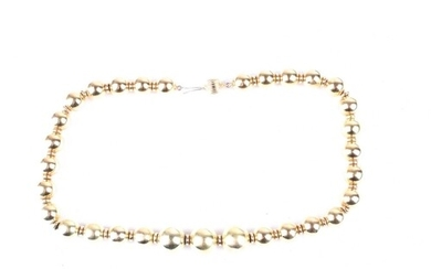 A graduated yellow metal bead necklace, the polished spheres...