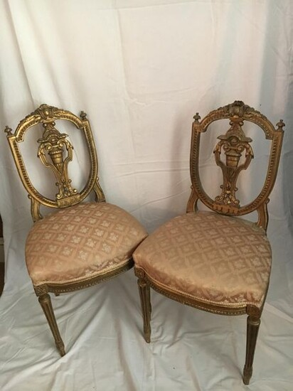 A pair of carved and gilded wooden chairs,...