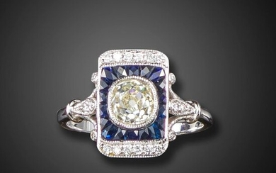 A sapphire and diamond rectangular cluster ring, the old cushion-shaped diamond is set within tapered calibre-cut sapphires and a border of diamonds in white gold, size N 1/2