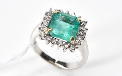 AN EMERALD AND DIAMOND CLUSTER RING-Centrally set with an emerald cut emerald weighing 3.10cts, surrounded by round brilliant cut di...