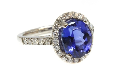 An 18ct white gold tanzanite and diamond oval halo cluster ring