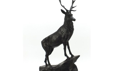Large patinated bronze stag raised on a stepped marble base,...