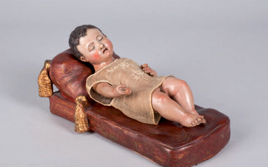 Sleeping child made of carved and polychrome wood. The cradle is made of polychrome and golden terracotta.