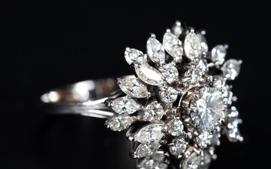 A DIAMOND CLUSTER RING claw set to the centre with a brillia...
