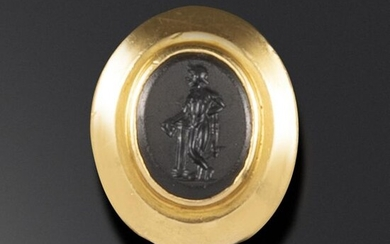 A Roman onyx intaglio depicting Dionysus, c1st - 2nd century AD, Dionysus depicted leaning on a column and holding a kantharos, in a 19th century gold ring mount, intaglio 1.1cm high, ring size L