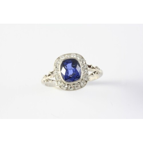 A SAPPHIRE AND DIAMOND CLUSTER RING the cushion-shaped sapph...