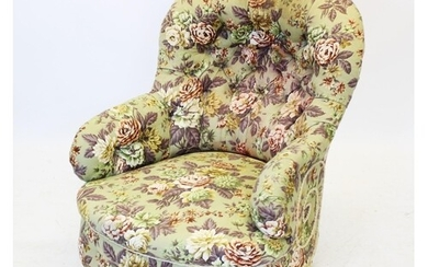 A Victorian button back tub chair, covered in floral pattern...