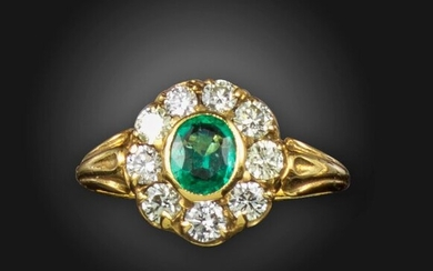 An emerald and diamond cluster ring, the oval-shaped emerald is set within a surround of round brilliant-cut diamonds in gold, emerald approximately 0.85cts, diamonds approximately 0.70cts, size M