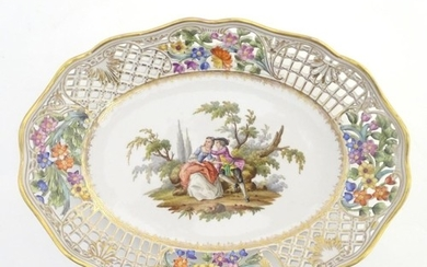 An oval basket dish with a reticulated floral border with gi...