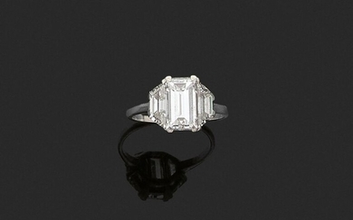 JANESICH. RING in platinum 850 thousandths, decorated with a rectangular diamond between two trapezoid diamonds. Signed and numbered. Finger size : 51. Gross weight : 3 g. Presumed weight of the diamond: 1.8 to 2 ct. (missing at one corner of the...