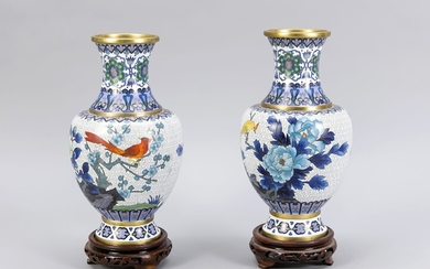 Pair of cloisonné vases, China, 20th cent. Decoration with birds between flowers and twigs against a white background, set off by borders. Neck with appropriate decoration. On a round, open worked wooden bases, h. without base 26 cm