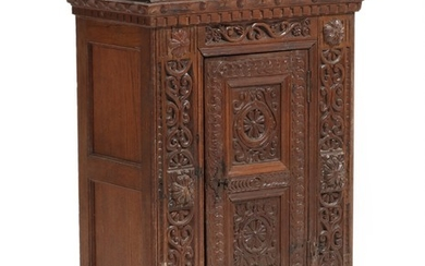 A Danish 18th century richly carved oak Regence cabinet, front with door. H. 96. W. 67. D. 37 cm.