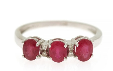 A ruby and diamond ring set with three oval-cut rubies and four brilliant-cut diamonds, mounted in 18k white gold. Size 55.