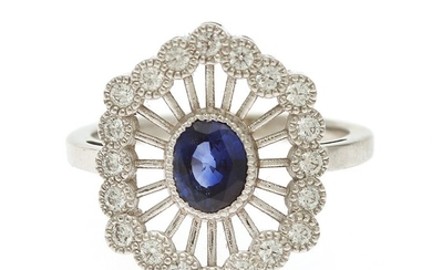 A sapphire and diamond ring set with an oval-cut sapphire encircled by numerous brilliant-cut diamonds, mounted in 14k white gold. Size 53.