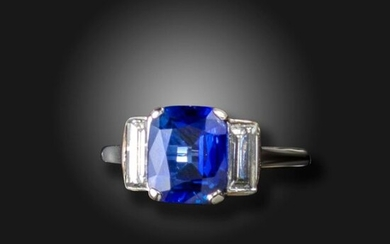 A sapphire and diamond three stone ring, the cushion-shaped sapphire is flanked with baguette-shaped diamonds in platinum, size Q, case Accompanied by report number 80274-55 dated 4 September 2020 from GCS stating that the cushion-cut sapphire weighs...
