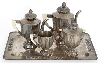 Coffee and tea set in partially embossed and carved silver with a floral decoration including a coffee pot, a teapot, a sugar bowl, a milk jug and a rectangular tray. Ivory handles.