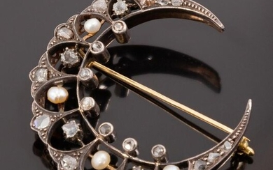 Moon-shaped brooch in 18k (750 thousandths) silver and yellow gold decorated with diamond chips, three-sided diamonds and rose-cut diamonds. Four pearls, probably fine, illuminate the whole. This type of brooch was very popular at the beginning of the...