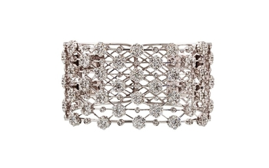 A DIAMOND SET CUFF BANGLE, set with daisy clusters of approx...
