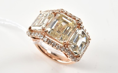 A MOISSANITE AND DIAMOND DRESS RING IN 18CT ROSE GOLD. APPROXIMATE TOTAL MOISSONITE WEIGHT 11.18CTS, APPROXIMATE TOTAL DIAMOND WEIGH...
