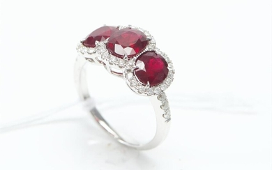 A THREE STONE RUBY AND DIAMOND DRESS RING IN 18CT WHITE GOLD, THE RUBIES TOTALLING 3.69CTS AND DIAMONDS ESTIMATED 0.50CT, SIZE M, 4....