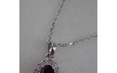 A diamond and garnet set pendant on an 18ct gold chain