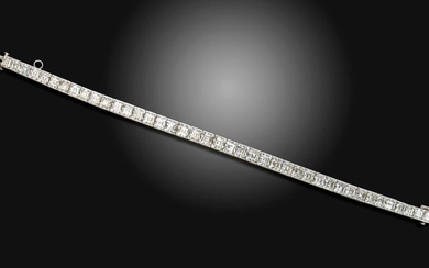 A slightly graduated diamond line bracelet, c.1925, the square-shaped diamonds channel-set in platinum, 17.5cm long Accompanied by report number 78131-57 dated 20 November 2017 from GCS stating that the square-cut diamonds weigh approximately 19.00cts...