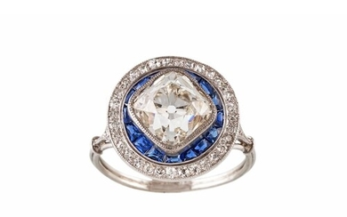 AN ART DECO DIAMOND AND SAPPHIRE TARGET CLUSTER RING, the ce...