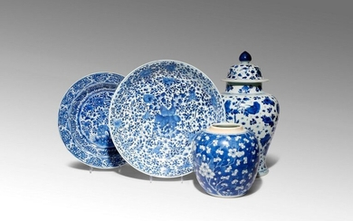 FOUR CHINESE BLUE AND WHITE ITEMS KANGXI 1662-1722 Comprising: an ovoid jar decorated with flowering prunus branches against a cracked-ice ground, a baluster vase and cover painted with butterflies amidst sprays of prunus, peony, chrysanthemum and...