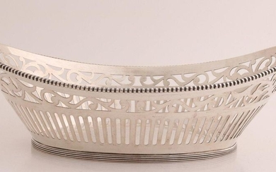 Silver bread basket, 835/000, oval sawn model with bars and floral pattern, provided with a soldered pearl rim. Placed on an oval ring with fillet edge, dent in. MT .: J. Krins, Schoonhoven, jl.:g:1966. about 335 grams. 27x18x9cm. In good condition