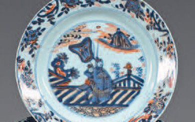 Two china plates. Kangxi (1662-1722). Imari decoration, in the center of Chinese in a landscape in a medallion with two circles, the wing of a frieze of flowering branches, net on the edge, the reverse with flowering branches, restoration on the edge...