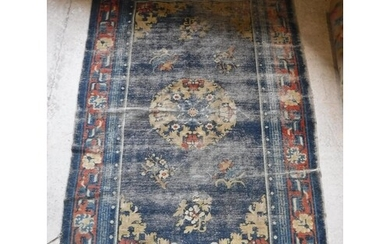 A Chinese rug, the central panel set with circular floral de...