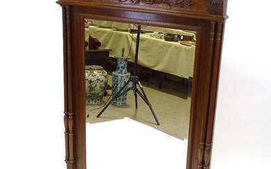 A French carved walnut-framed wall mirror, with fluted twin ...