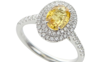 A SAPPHIRE AND DIAMOND DRESS RING IN 18CT WHITE GOLD, CENTRALLY SET WITH AN OVAL CUT YELLOW SAPPHIRE OF 1.32CTS, WITHIN A SURROUND O...