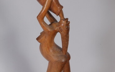 AFRICAN WOODEN FIGURE CARVED AS ATTENUATED WOMAN DRINKING FROM VESSEL....