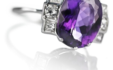 An Art Deco amethyst and diamond ring set with an amethyst weighing app. 5.00 ct. flanked by numerous old and princess-cut diamonds, mounted in 14k white gold.