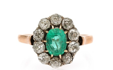 An emerald and diamond ring set with an oval-cut emerald encircled by ten old-cut diamonds, mounted in 18k rose gold and silver. Size 52.5.
