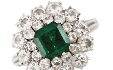 Platinum ring with emerald surrounded by a double...