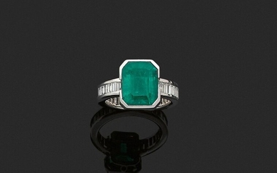 RING in 750 thousandths white gold decorated in the centre with a rectangular cut-faceted emerald, the ring entirely set with rectangular diamonds. Finger circumference: 55.5. Gross weight: 9.1 g. Assumed weight of the emerald, about 6.08 ct...