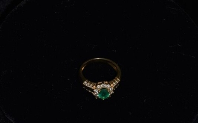 Ring in 18 k yellow gold set with a 0.7 k emerald with small diamonds . Weight 6 grams .