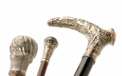 Two early 20th century wood and silvered metal walking sticks, one wrapped in leather. L. 87–91 cm. (3)