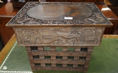 A Chinese wooden scholar's desk ornately carved with dragons...
