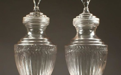 A LARGE PAIR OF CUT GLASS PEDESTAL URNS AND COVERS.