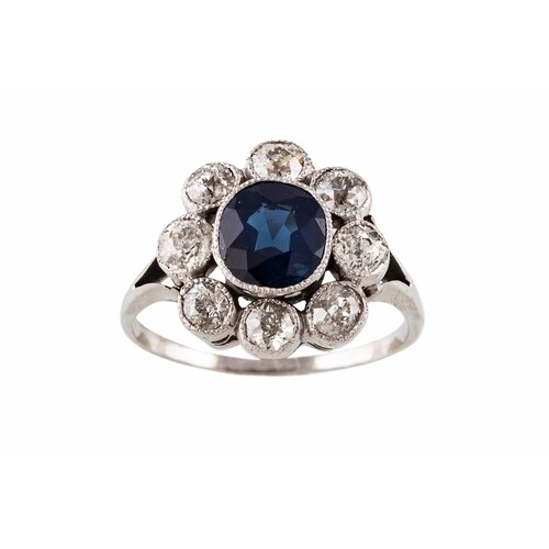 A SAPPHIRE AND DIAMOND CLUSTER RING, the oval sapphire to an...