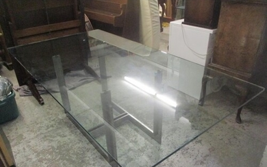 A large glass topped dining table in the style of a Sarpi ta...