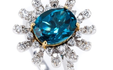 AN 18CT WHITE GOLD TOPAZ AND DIAMOND STARBURST RING; centring on a 2.8ct oval cut London blue topaz to surround and shoulders set wi...