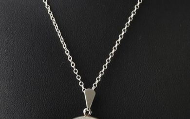 AN ENGLISH OVAL LOCKET WITH ENGRAVED FLORAL DECORATION IN STERLING SILVER, WITH CHAIN