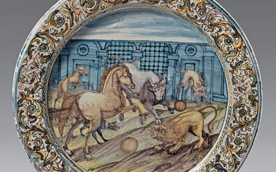 Italian earthenware dish (Castelli, Grüe's workshop) from the middle of the 17th century. With blue, green, ochre and manganese decoration, in the centre of a scene with an animal fight in an architectural landscape, the wing of coat of arms in a...