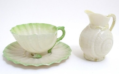 A Belleek tea cup and saucer of shell form with green