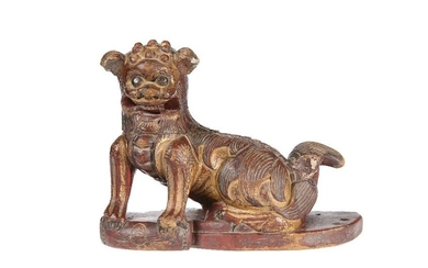 A CHINESE CARVED WOODEN MODEL OF A FOO DOG, gilded and